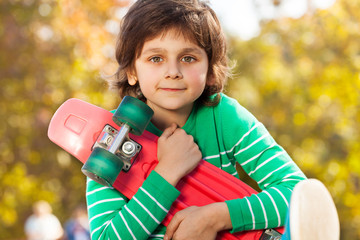 Happy boy in green sweater with red skateboard