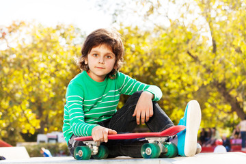 Small boy in green sweater holds red skateboard