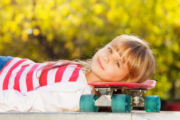 Portrait of beautiful girl with head on skateboard