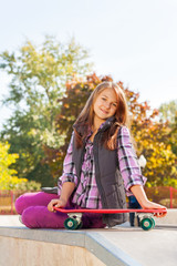 Positive girl holds skateboard sits on ground