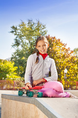 Smiling girl with braid holding red skateboard