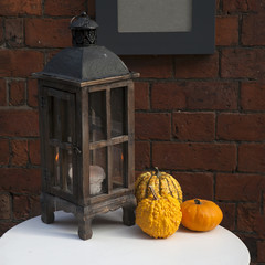wooden lantern with pumpkins as decoration of interiour