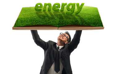 Green energy concept,Businessman holding open book with green tr
