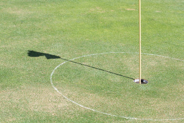 golf hole on green grass with shadow flag