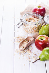 Fresh fruits and rolled oats over white background