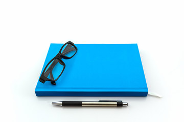 Blue book with glasses and pen .