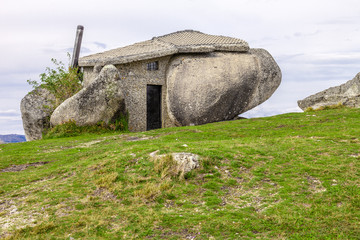 House built between huge rocks on top of a mountain