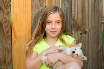 blond kid girl hug a puppy dog chihuahua on wood
