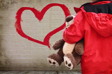 Kind vor einer Mauer mit Herz