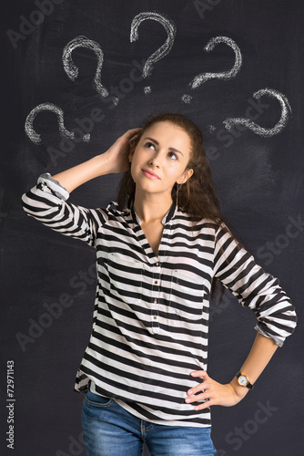 canvas print picture A shot of attractive young woman standing in front of a blackboa