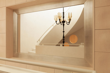 Elegant chandelier and stairs riflection into the mirror