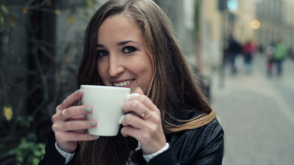 Young happy attractive woman drinking coffee in cafe