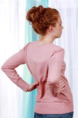 junge Frau mit Rückenschmerzen