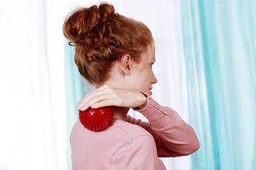 Frau mit Igelball bei Schulterverspannungen