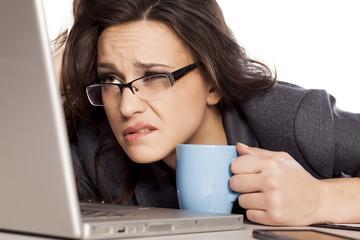 sleepy and tired business woman on laptop, holding a coffee mug