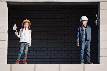 little boy and girl in helmets build house