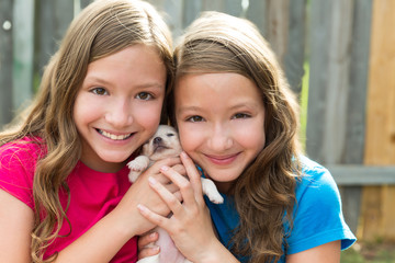 Twin sisters and puppy pet dog chihuahua playing