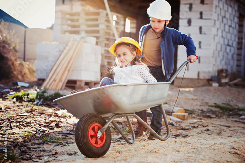 boy and girl playing on construction site - 72976787