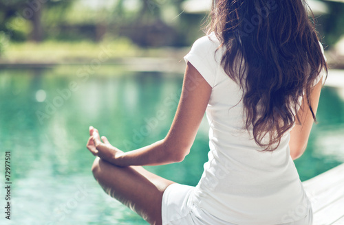 Slim Woman Meditating at the Poolside - 72977501