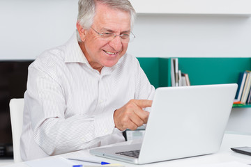 Mature man looking surprised on her laptop screen