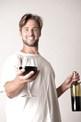 Young man relaxing with a bottle of red win
