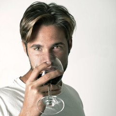 Young man relaxing with glass of red win
