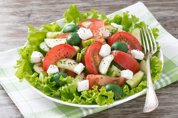 green salad with vegetables and feta on a plate