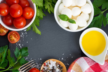 Mozzarella, ingredients for the salad and black background