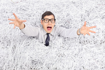 Terrified man drowning in a pile of shredded paper