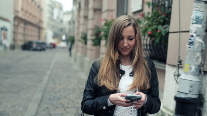 Woman with smartphone walking in the city, steadicam shot
