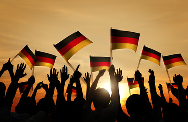 Silhouettes of People Holding Flag of Germany