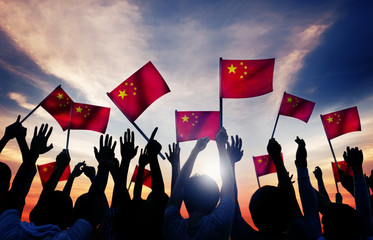 Silhouettes of People Holding the Flag of China