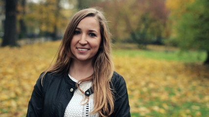 Portrait of young happy woman in autumn park