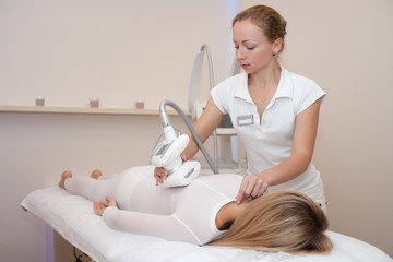 young woman on a lipomassage procedure in beauty salon