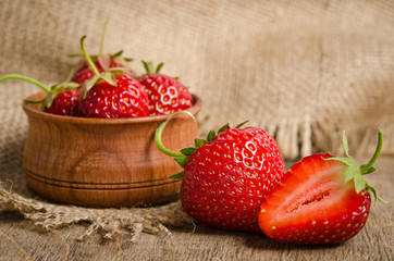 Ripe Strawberry in a wooden Bowl on burlap background