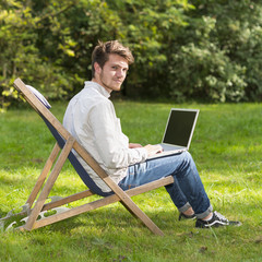 Portrait of young man on profile sitting with laptop computer