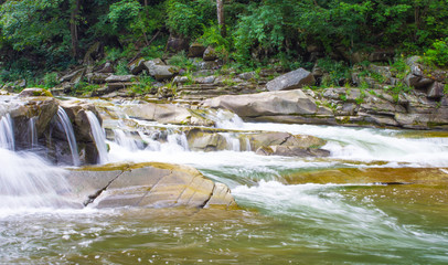Beautiful scenery with river at mountains and little waterfall