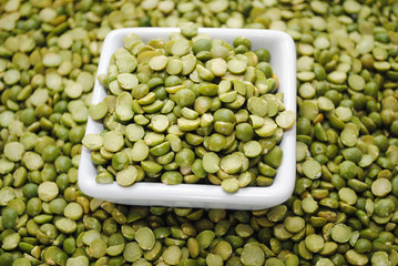 Split Green Peas in a Square Bowl Over a Background of Peas
