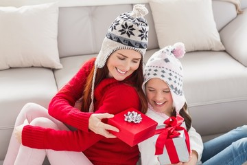 Mother and daughter exchanging gifts at christmas