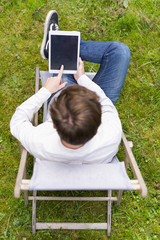 Bird view on young man, tablet and screen touch in garden