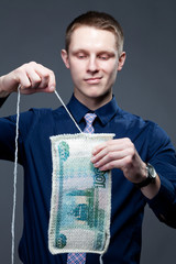 Businessman disincorporate a banknote as a knit fabric