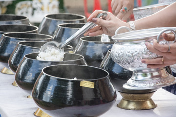 puts food offerings in a Buddhist monk's alms bowl