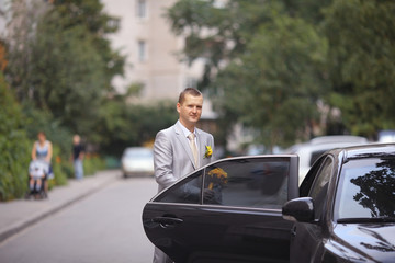 groom sits in the car at a wedding