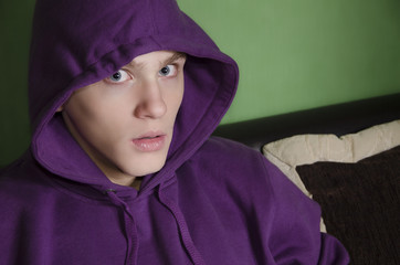 Scared kid with purple hood looking at camera. Anxiety