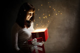 Beautiful  girl with magic holiday red gift on dark background