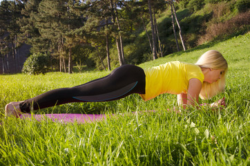 Young blonde doing plank in nature