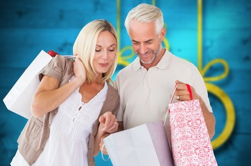 Composite image of happy couple with shopping bags