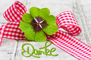vierblättriges Kleeblatt mit Geschenkschleife auf Holz, Danke