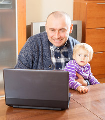dad sitting at  laptop with  young daughter