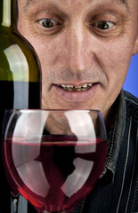man looking in a glass of wine